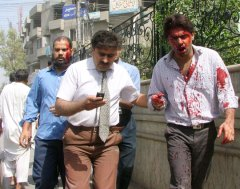 Injured men are seen near the site of the car bombing in Lahore, Pakistan on Wednesday, May 27, 2009. (AP / K.M. Chaudary)